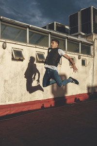 Stylish bboy performing a break dance jump showing his shadow in a white wall in the rooftop of a building