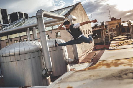 Stylish bboy performing a break dance jump between metallic pipes in the rooftop of a building