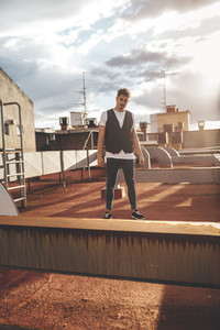 Portrait of a handsome man in the rooftop of a building at sunset