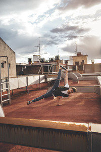 Stylish bboy performing a break dance stance metallic pipes in the rooftop of a building at sunset