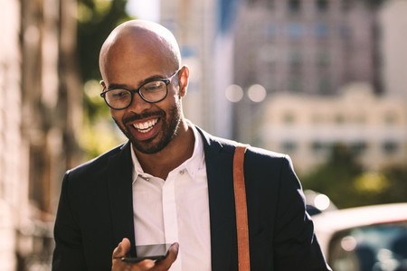 Businessman commuting with a mobile phone outdoors