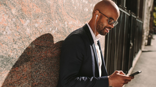 Businessman listening music with phone outdoors
