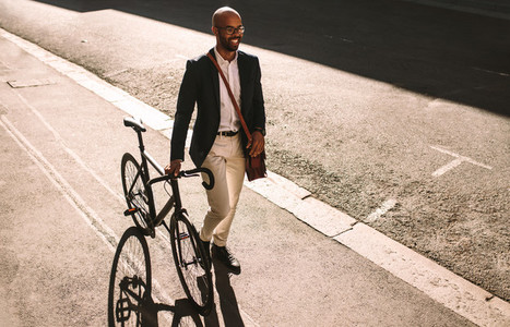 African businessman going office with his bike