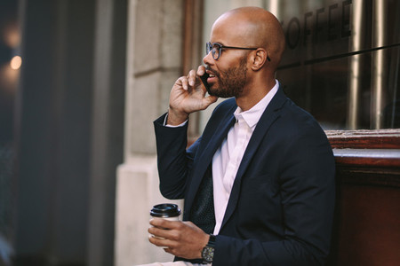 Businessman relaxing outdoors making a phone call