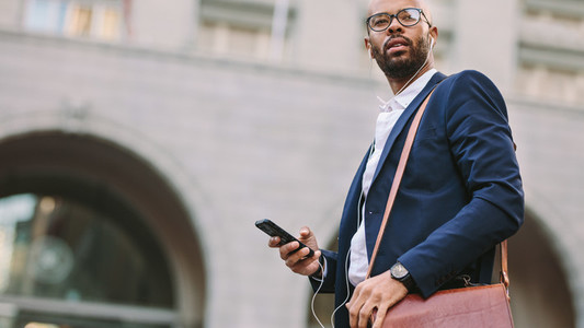 African businessman walking on city street