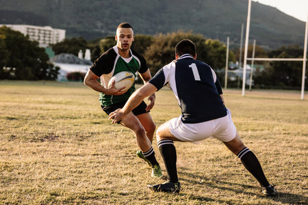 Rugby players tackling during game