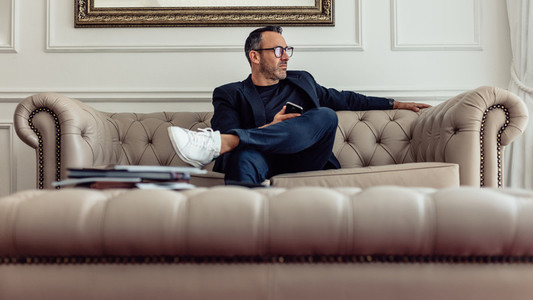 Stylish mature businessman sitting on couch in hotel room