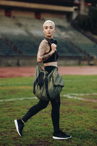 Fitness woman walking inside a track and field ground