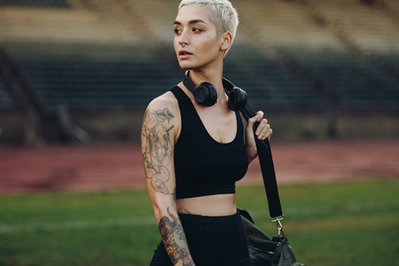 Portrait of a woman athlete walking in a stadium