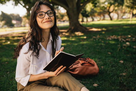 Pretty woman writing in book at park