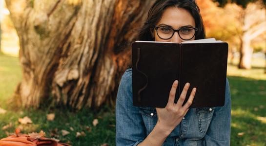 Woman peeking over a book at park