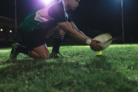 Rugby player placing the ball on tee for penalty