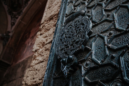 detail of cordoba mosque door carved in metal with patrons muslim