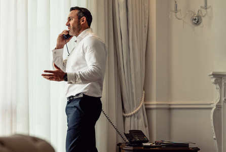 Man on business trip talking on hotel room phone