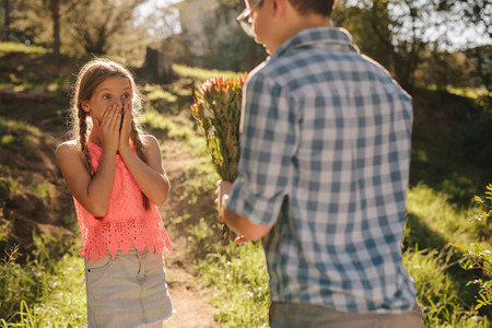 Boy giving a bunch of flowers to his girlfriend