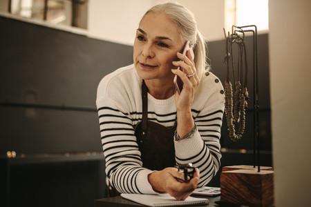 Jeweler in her workshop making a phone call