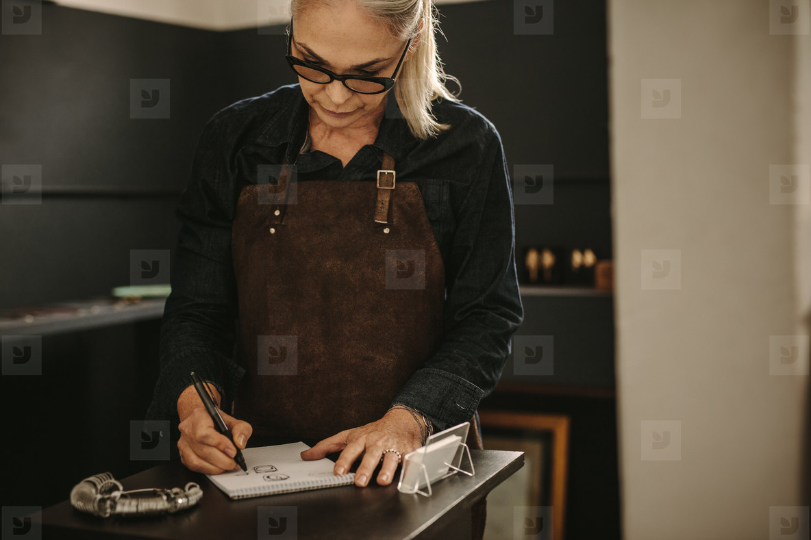 Jewelry designer sketching out designs in studio