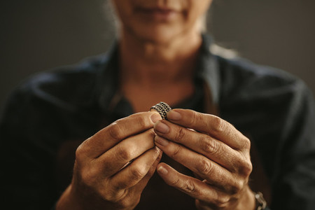 Jewelry maker hands inspecting a silver ring