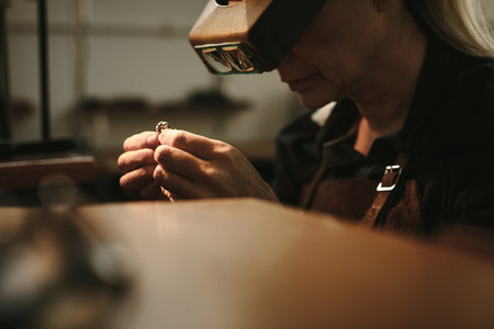Jewelry maker inspecting product with magnifying glass