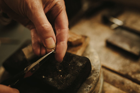 Female jeweler cutting small pieces of metal