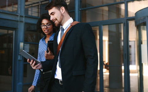 Business colleagues with digital tablet walking out of office