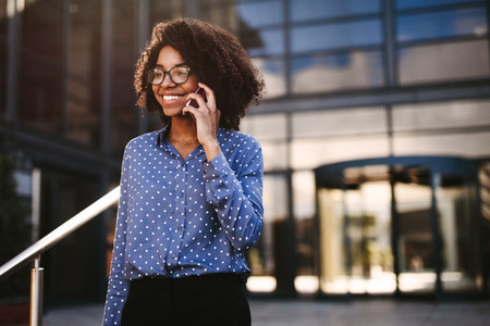 Female business professional walking outside using phone