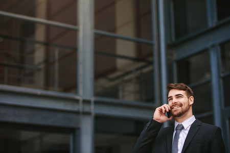 Positive businessman outdoors talking on phone