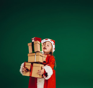 Little girl in santa claus dress carrying gift boxes
