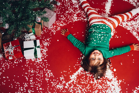 Kid lying on floor beside a christmas tree