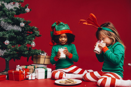 Kids drinking milk sitting beside a christmas tree