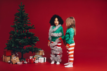 Kids having fun standing beside a christmas tree