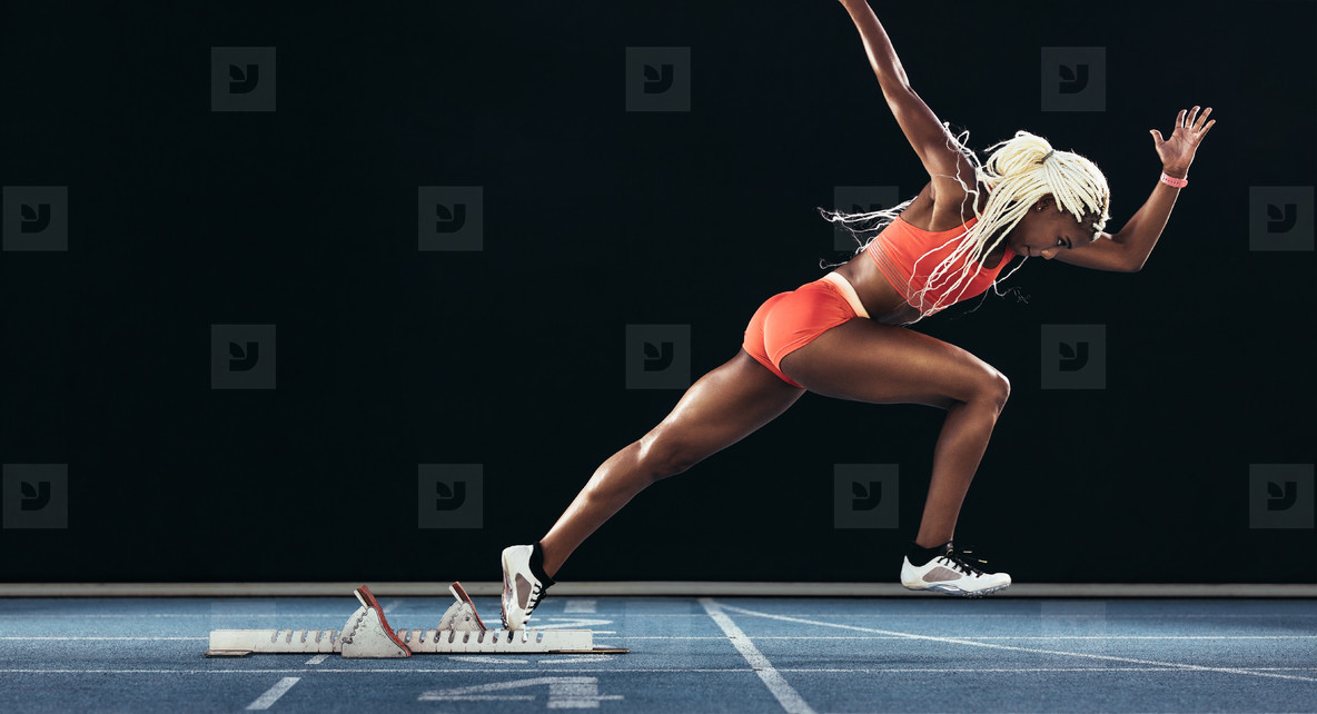 Female sprinter taking off from starting block on a running trac