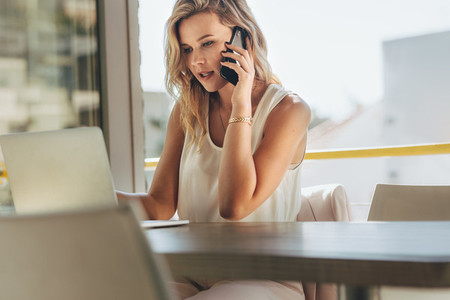 Businesswoman talking with client over phone in cafe