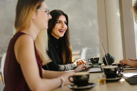 Multi ethnic businesswomen having break during meeting