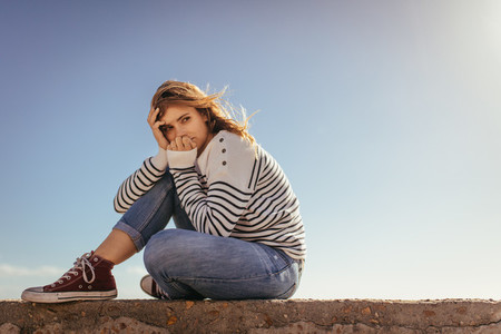 Woman sitting on a sea wall looking away