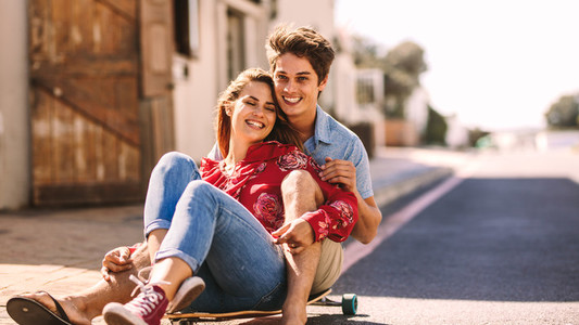 Couple enjoying a skateboard ride together on a street