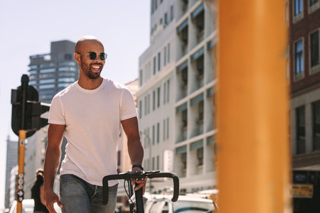 Handsome man enjoying city walk with a bicycle