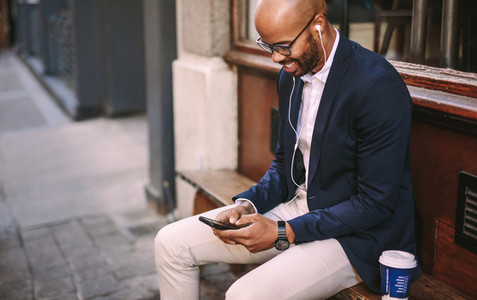 Happy businessman listening music with phone outdoors