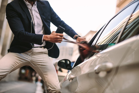 Businessman pulling out his handbag from a car