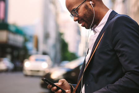 Businessman commuting with a smartphone on city street