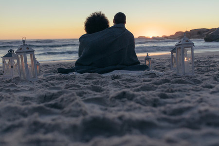 Couple sitting on the beach at sunset