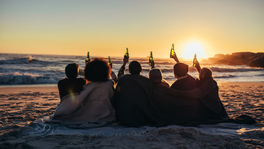Group of friends enjoying beach sunset with beers