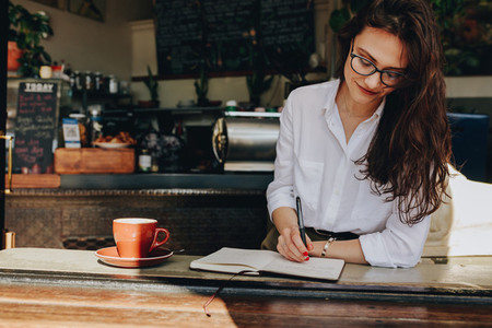 Woman sitting in the cafe writing notes in her diary
