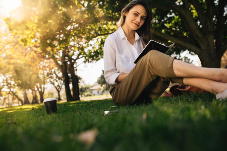 Pretty young woman sitting at park with book