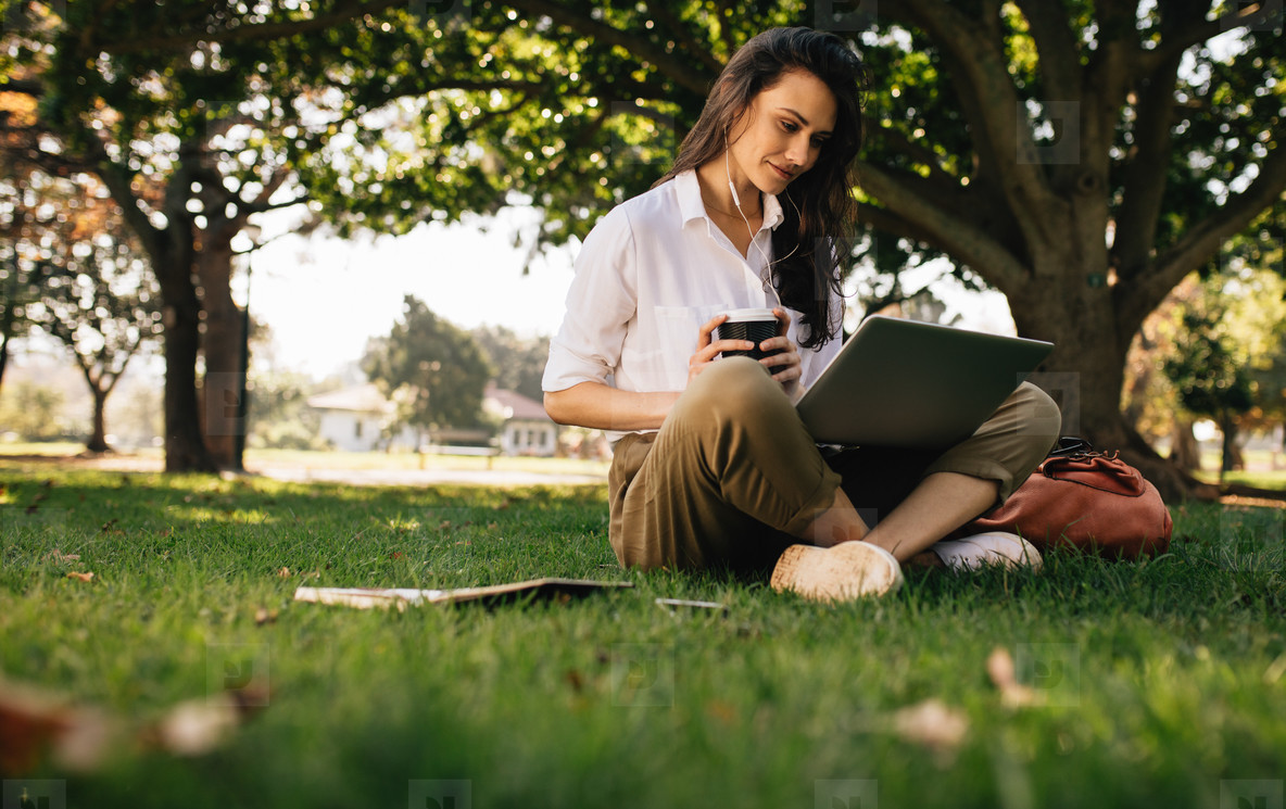 Woman at park with coffee watching video on laptop