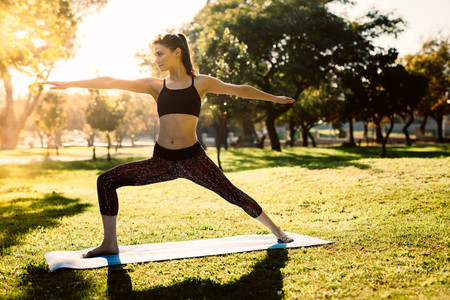 Fit woman doing yoga at park