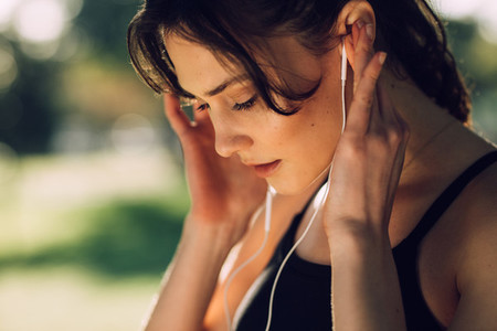 Fitness woman listening to music wearing earphones