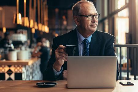 Senior businessman sitting at coffee shop with laptop
