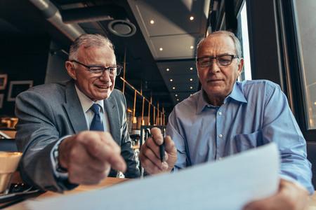 Senior business men discussing at financial report