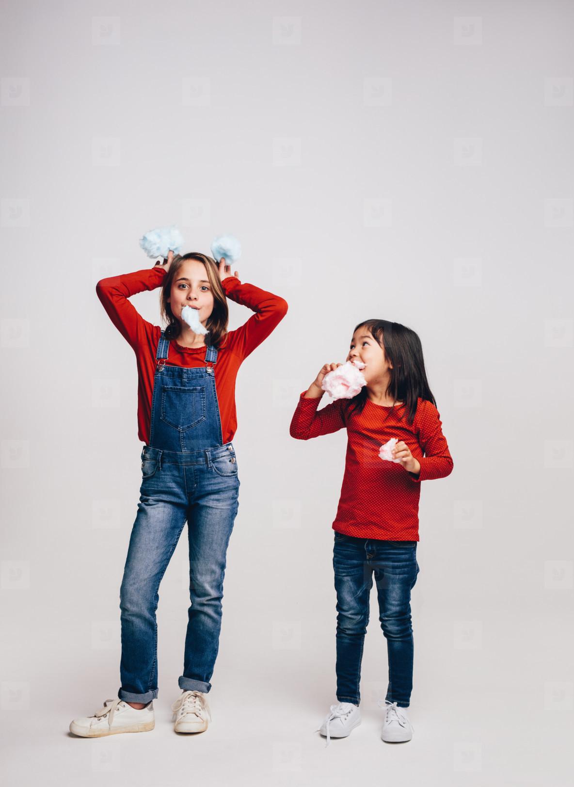 Girls having fun eating candy floss